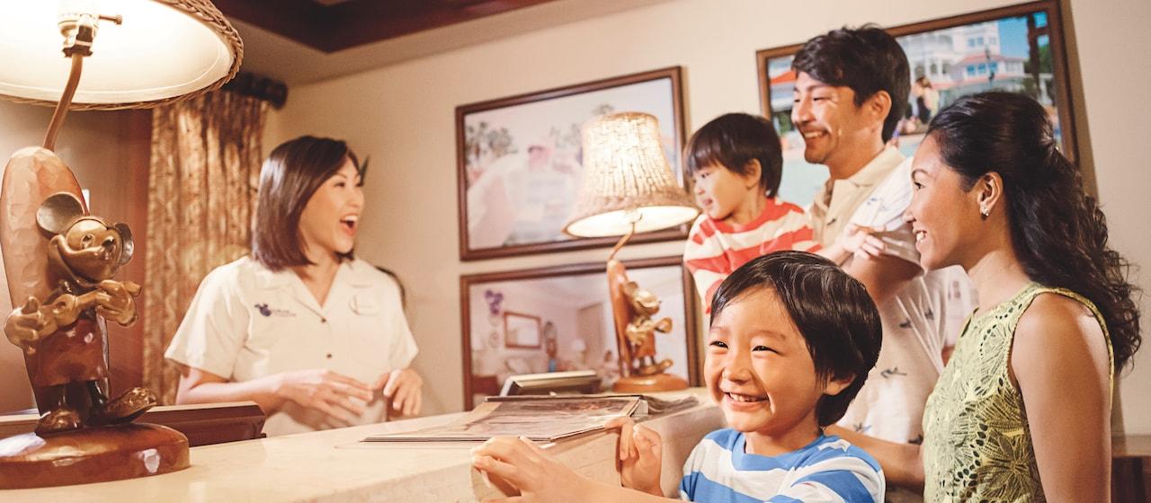 カウンターにいるディズニー・バケーション・クラブ・ガイドと話をする両親と 2 人の少年