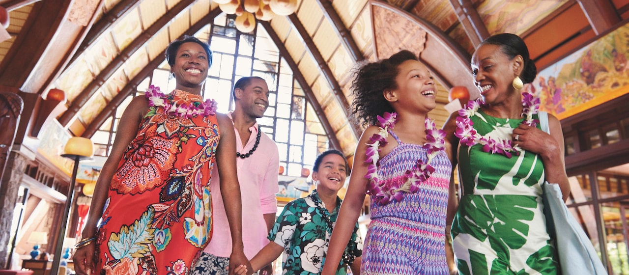 A family of 5 are all smiles as they walk through the lobby of an Aulani Resort building dressed in Hawaiian outfits and leis