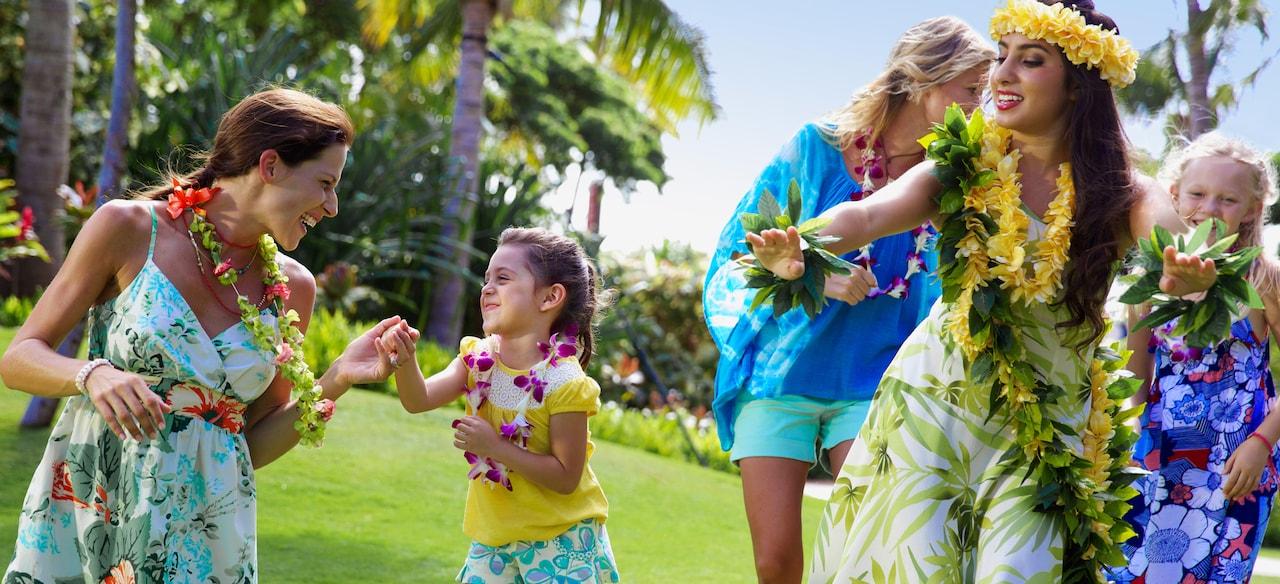 ハワイのフラダンス・レッスンを体験する花のレイをかけた 2 人の少女とその母親たち