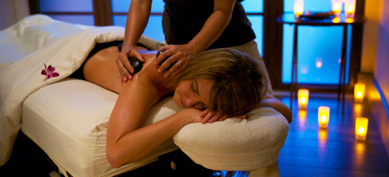 A woman lies on a massage table as a masseuse rubs hot stones on her back at the Laniwai Spa