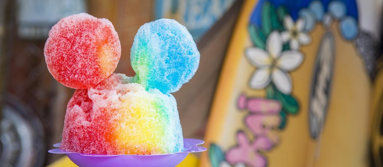 サーフボードをバックに、ミッキーの耳の形をつけた虹色のシロップに彩られたパパルア・シェイブアイスのかき氷