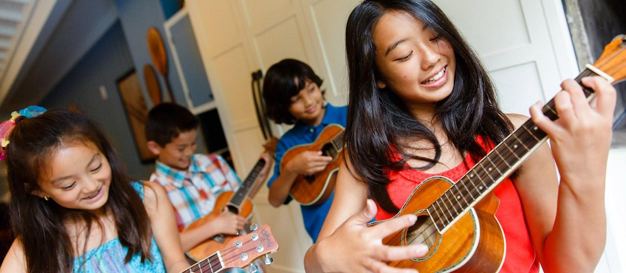 パウハナ・コミュニティ・ルームで楽しそうにウクレレを弾く、赤や青のドレスを着た少女と、その後ろでチェックの服と青い服を着た少年たち。