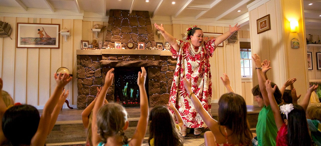 A woman in Hawaiian garb and a group of children sitting on the floor watching her reach to the sky