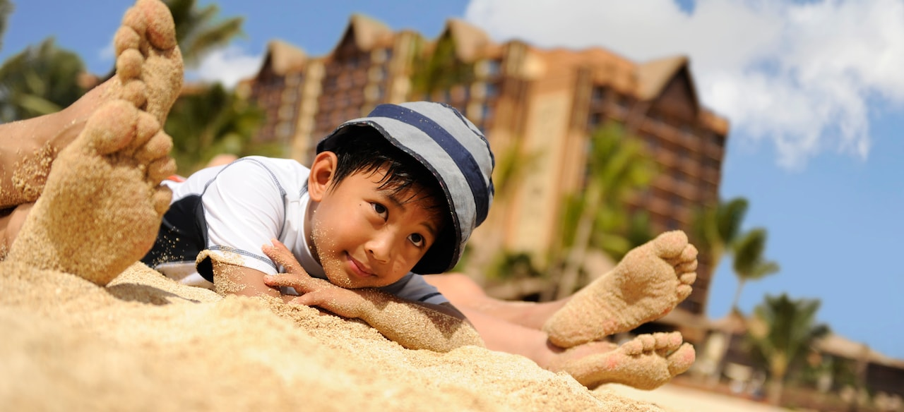 A boy lies on the sand, daydreaming between 2 pairs of sandy feet