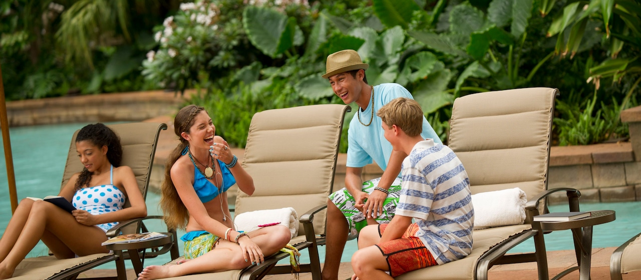 A group of 2 teen girls and 2 teen boys laugh and read on chaise lounge chairs by a pool