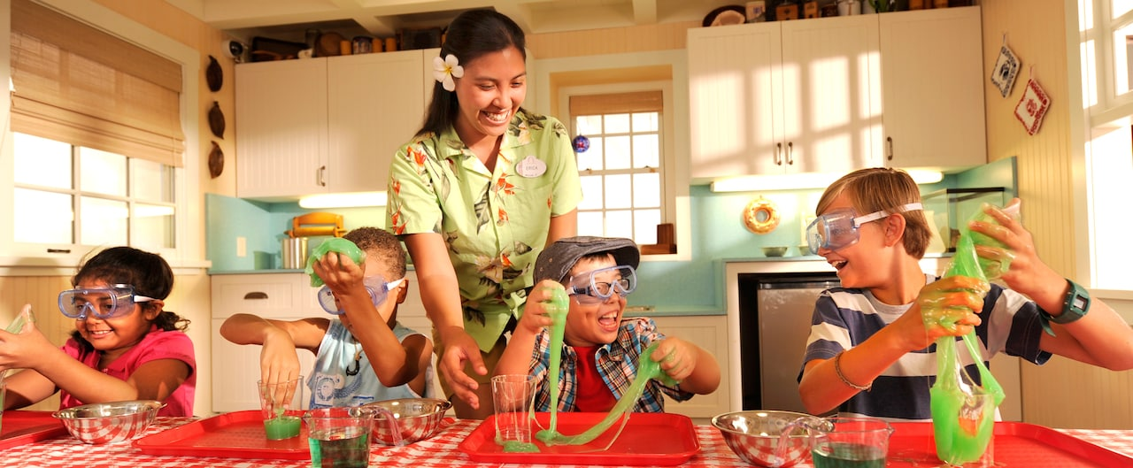 A Cast Member supervises 4 children wearing goggles and playing with green slime
