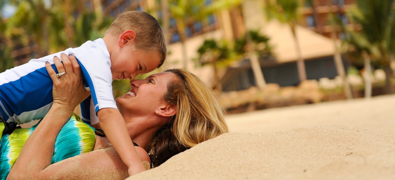 A smiling mother lies on a beach, holding her young son above her, their noses pressed together