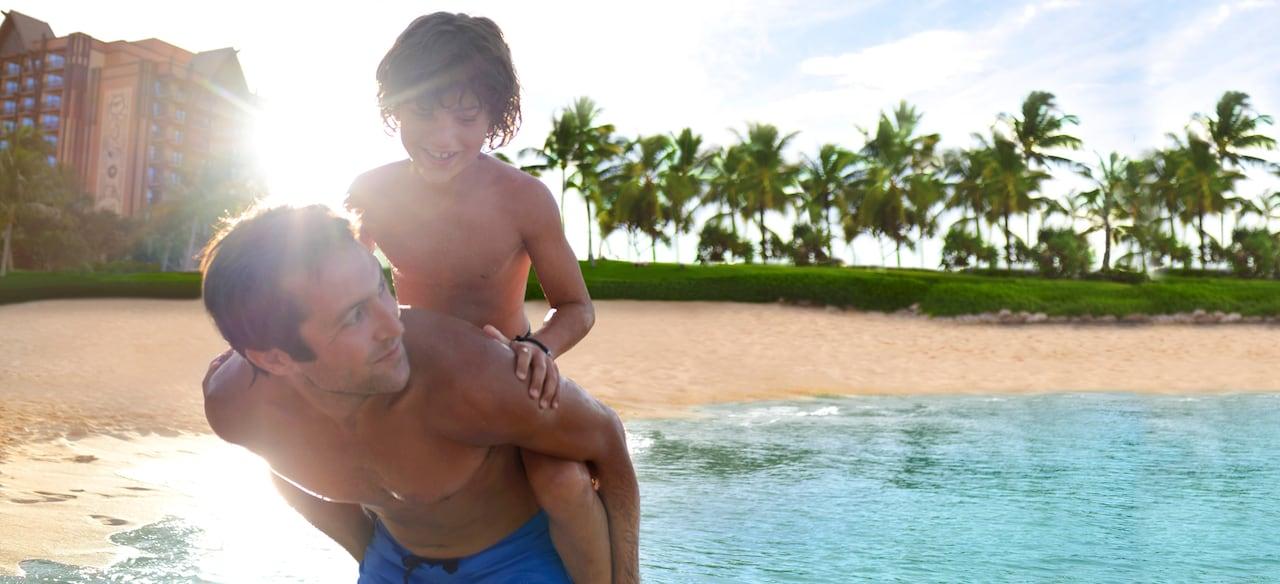 南国のビーチで父親の背に乗って微笑む少年
