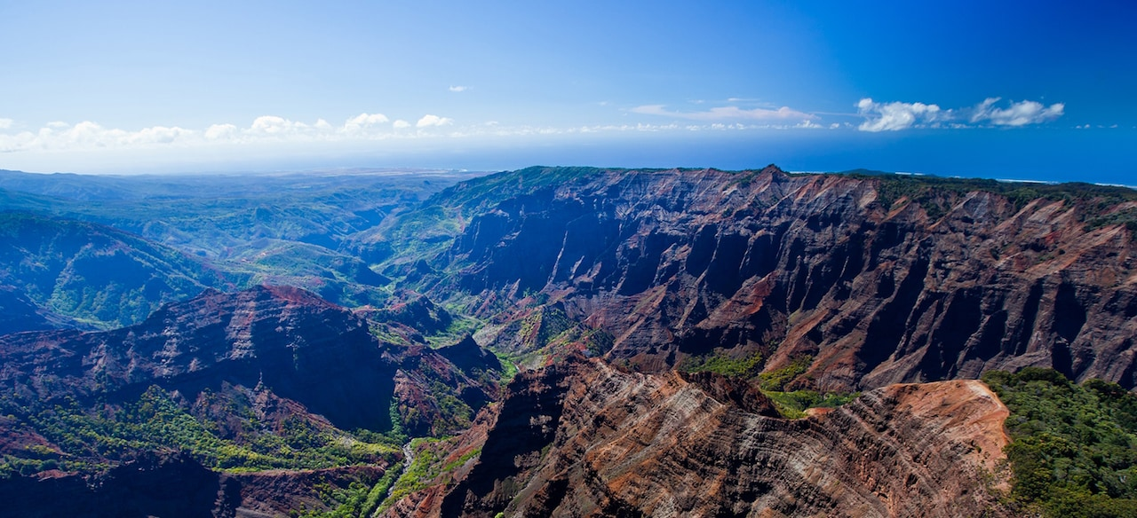 A sweeping panoramic view of rugged canyons and lush green valleys