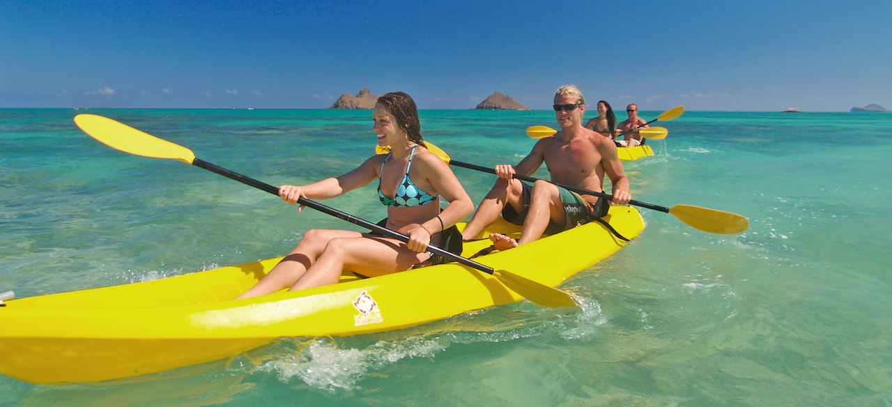 Two couples paddle their kayaks in the open ocean