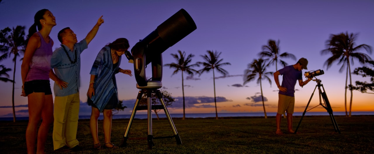 A Cast Member points skyward, a young woman listens and another looks through a large telescope
