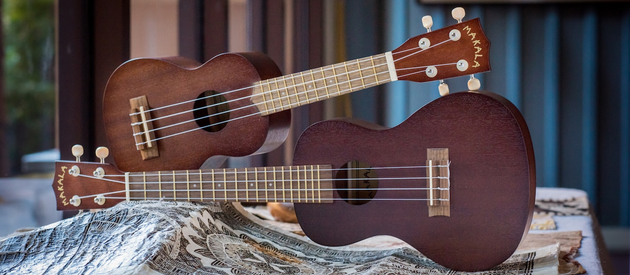Two 'ukuleles, one on top of the other, lay on their sides on a table with a small mat beneath them