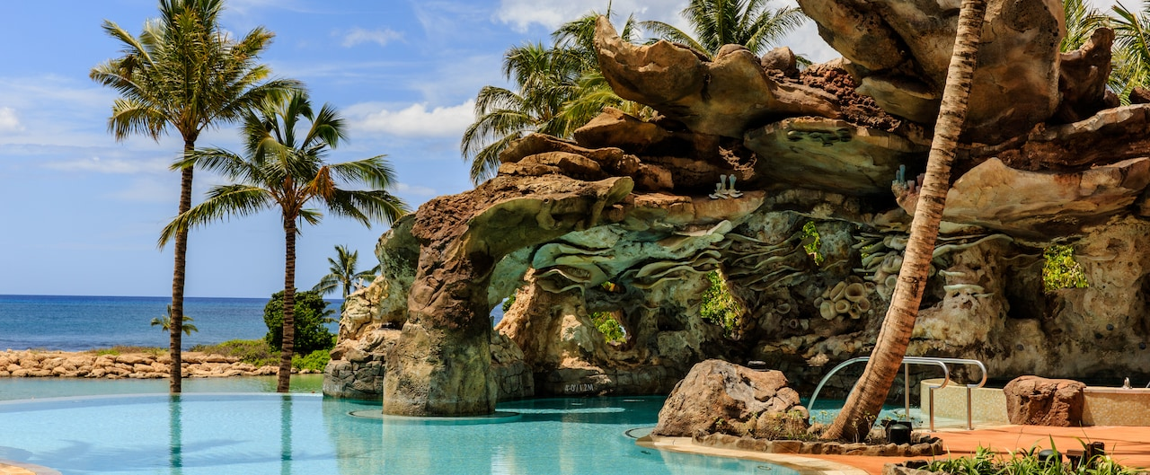 A couple unwinds in the waters of the Ka Maka Grotto oceanfront pool near the ocean