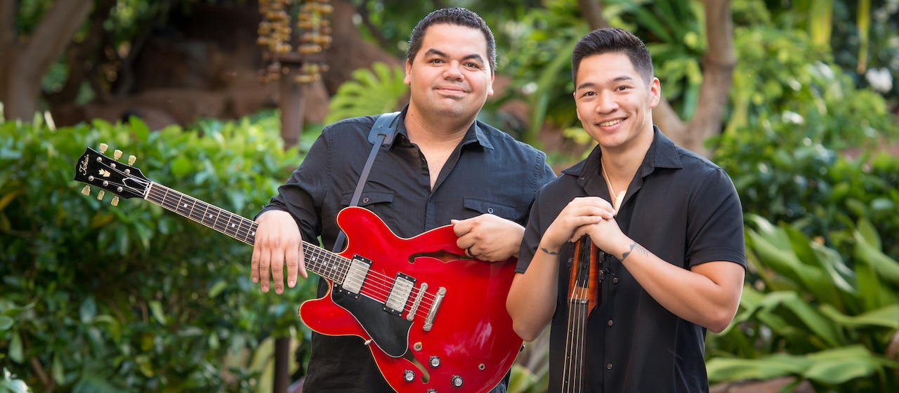 Musicians Halehaku Seabury-Akak, who holds a guitar, stands next to Nicholas Lum, who leans on his bass guitar