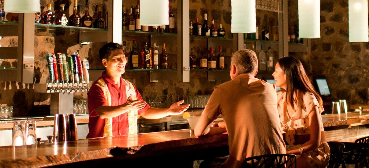 ペンダントライト照明の下、微笑みながら、座っているカップルと身振りを交えて話をしているバーテンダー