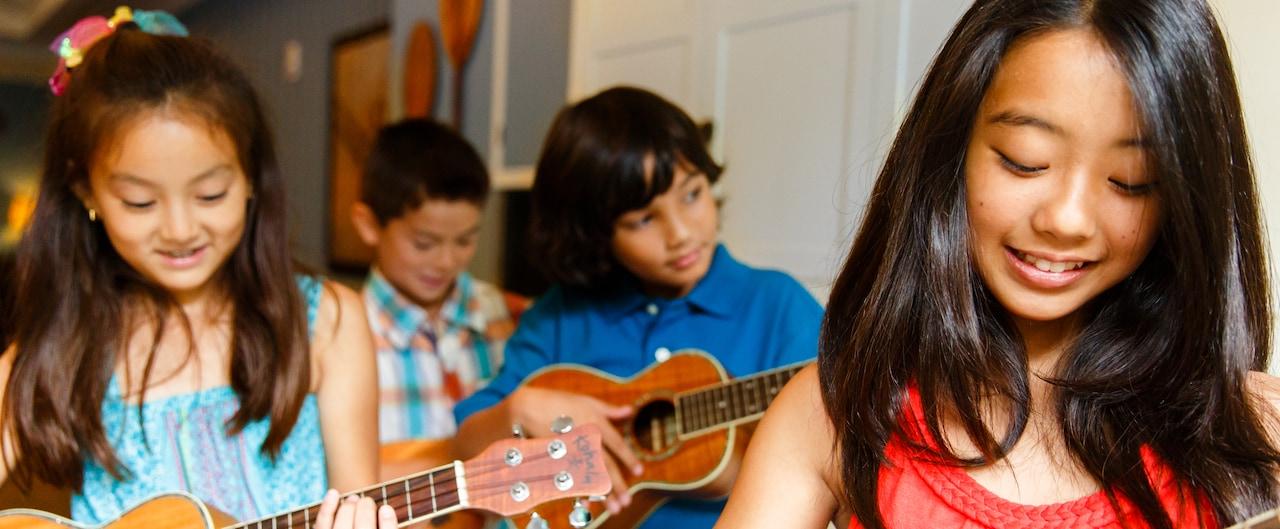 Two girls and 2 boys sit playing ukuleles