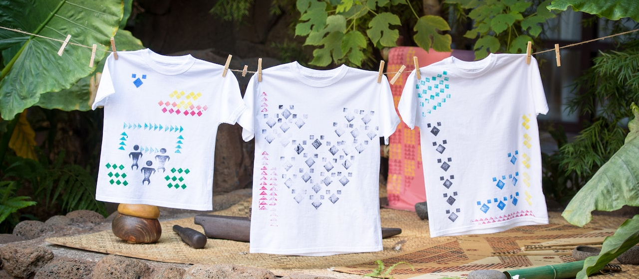 Three t-shirts with kapa stamp designs are hung on a line with clothespins