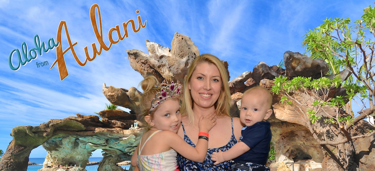 A smiling family strikes a pose in front of a Green Screen backdrop featuring the Aulani Resort