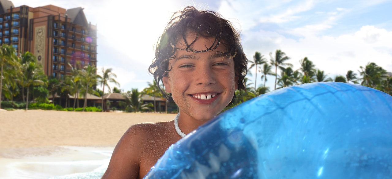 A boy wades into the ocean at Aulani Resort holding a blue inflatable float tube.