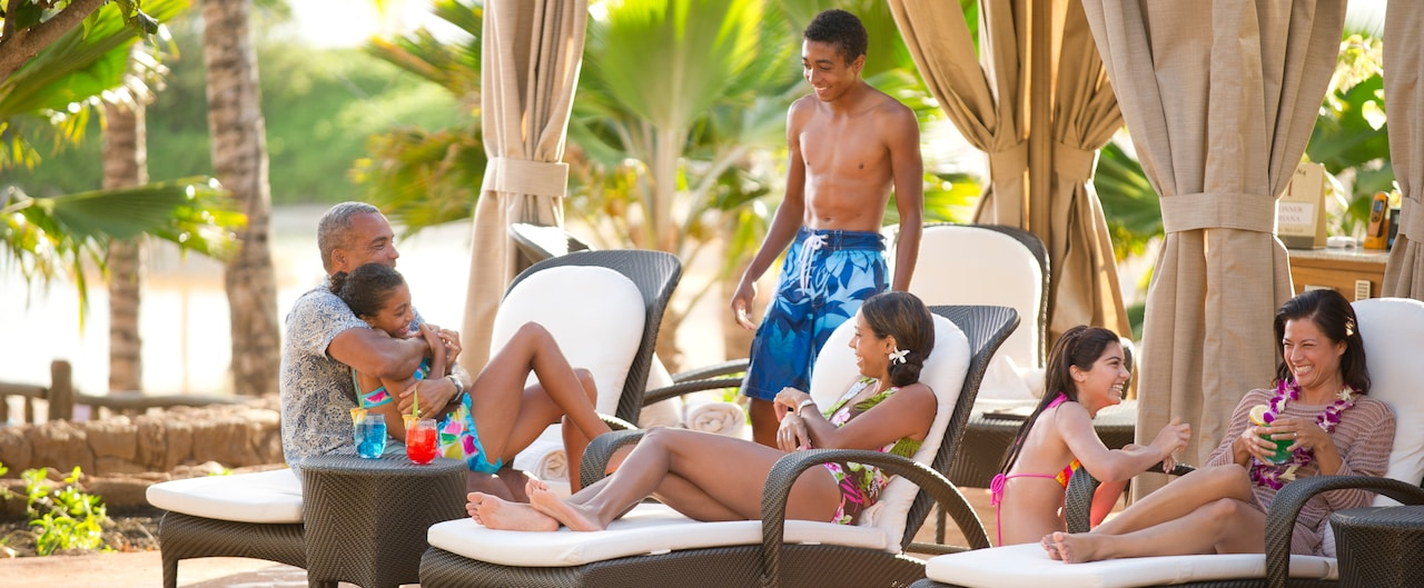 A family with 4 teenage children lounges on wicker furniture under a cabana awning