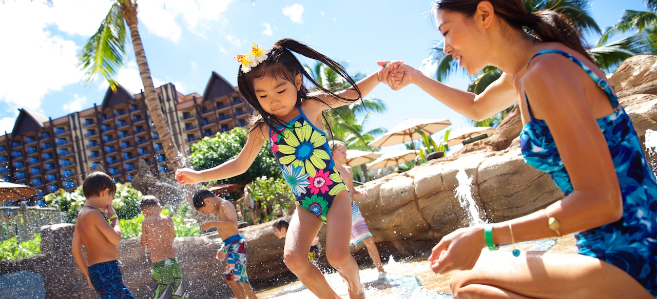 A mother holds her young daughter's hand as she plays in a paved area with squirting water jets