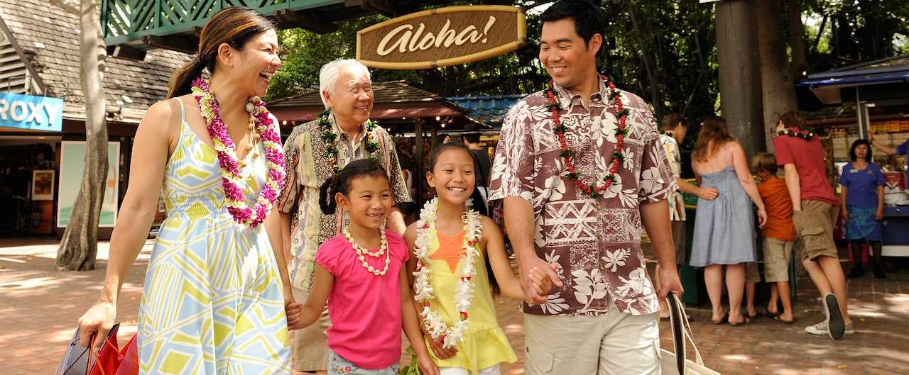 A mother, father, 2 girls and a grandfather stroll along an outdoor shopping promenade