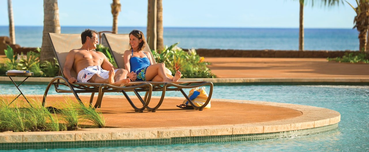 A man and woman in swimwear sit poolside on lounge chairs near the ocean