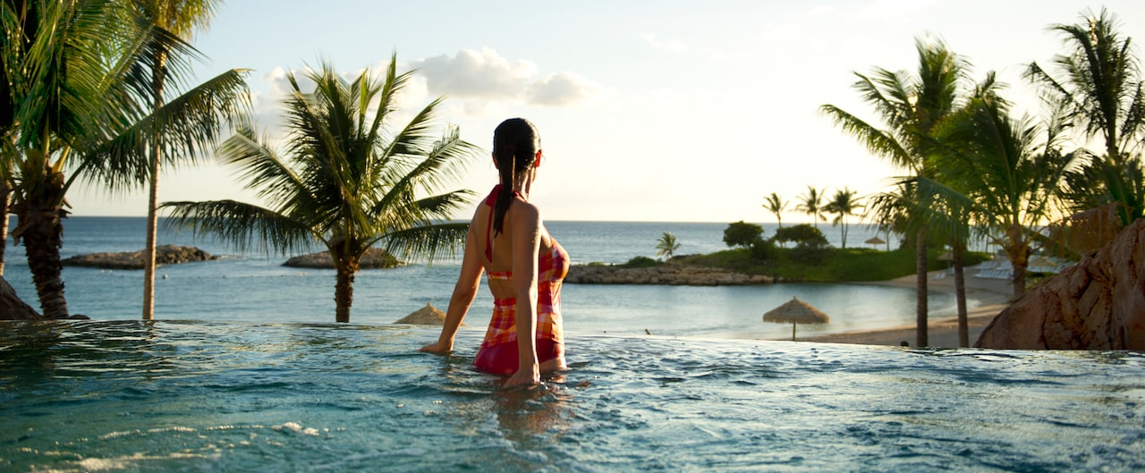 A female guest wearing a bathing suit enjoys a whirlpool spa while gazing at the clouds