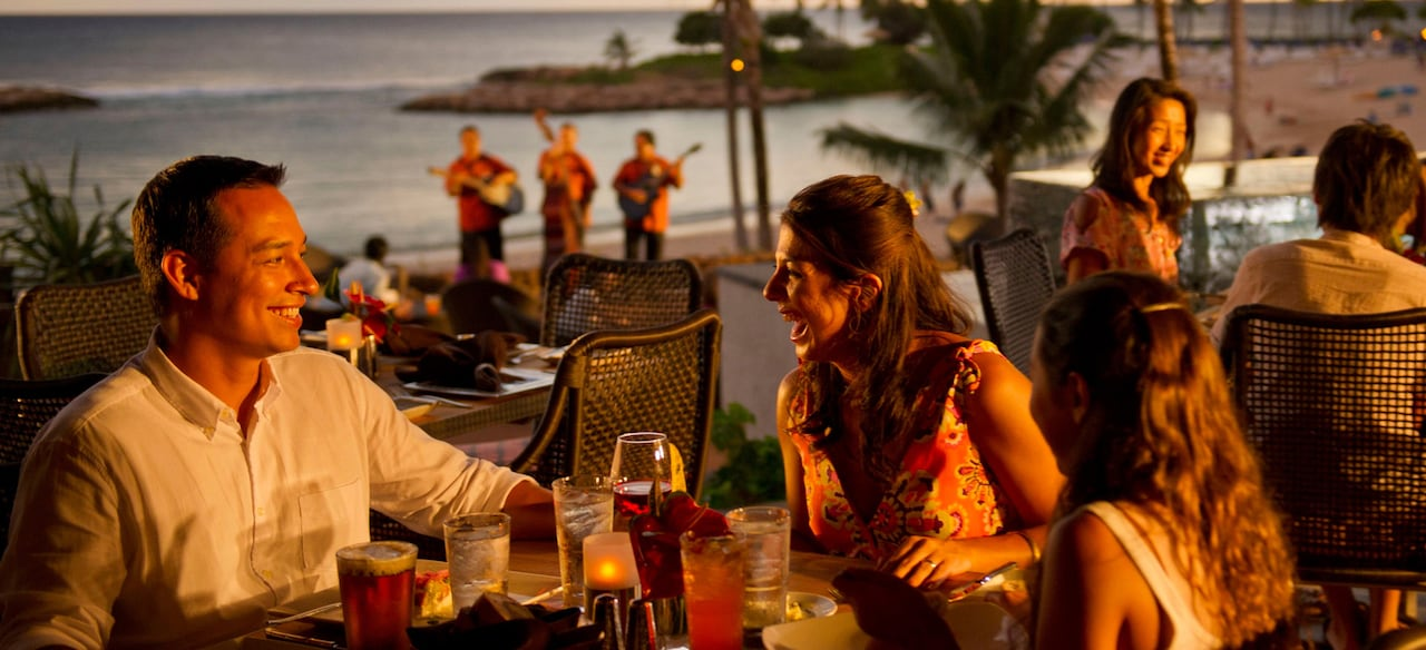 A father, mother and daughter enjoy drinks at an outdoor table with sunset ocean views and live musicians