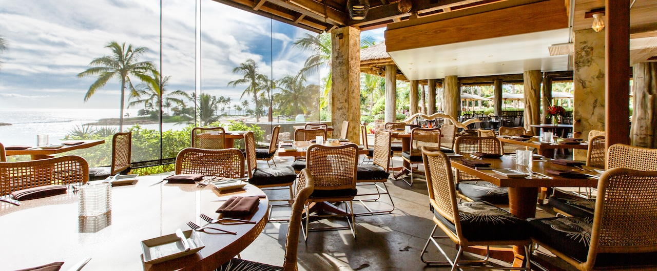 Tables on a covered patio look upon palm trees and ocean views through mesh screens