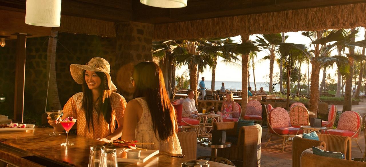 沈んでいく太陽を背景に、オープンエア・バーでカクテルとアペタイザーを味わう 2 人の女性