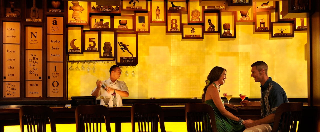 A young couple sits in a stylish bar gazing into each other's eyes while a bartender mixes a drink