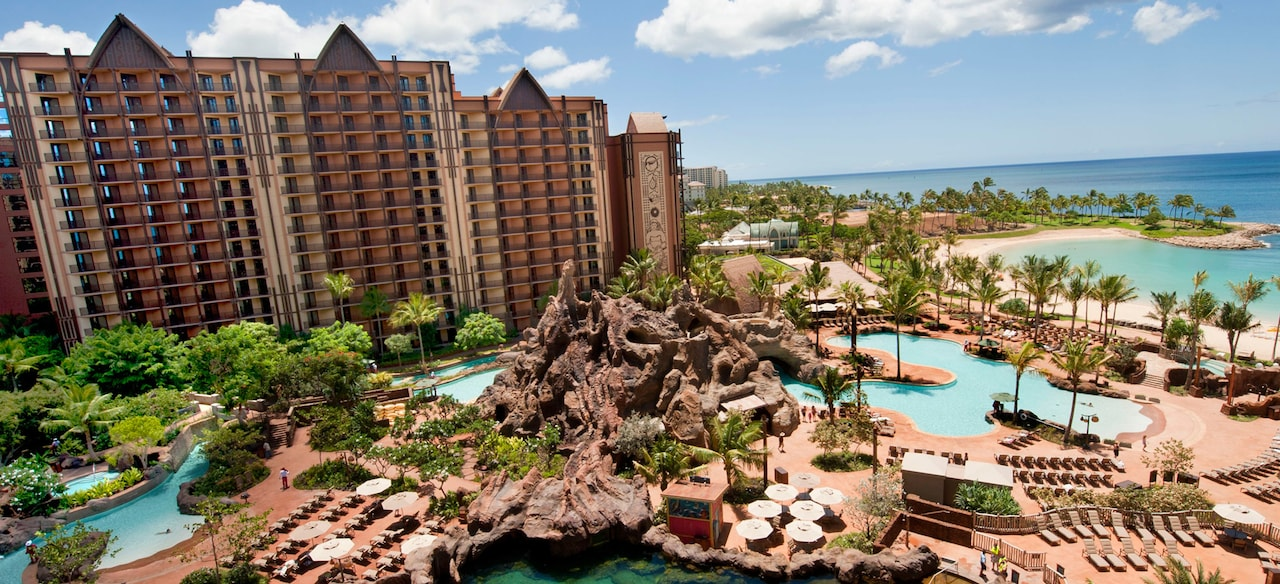 A large pool area includes a volcano waterslide feature, lounge chairs and a palm trees