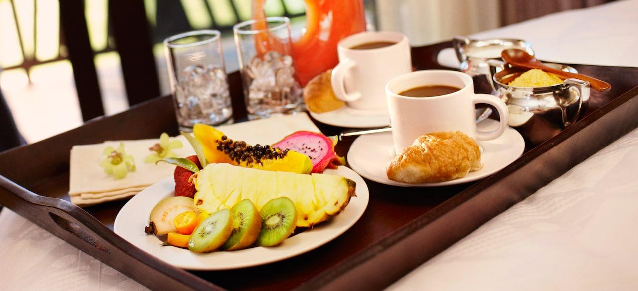 トロピカルフルーツ、コーヒー、クロワッサン、ジュースの朝食が乗ったルームサービスのトレイ