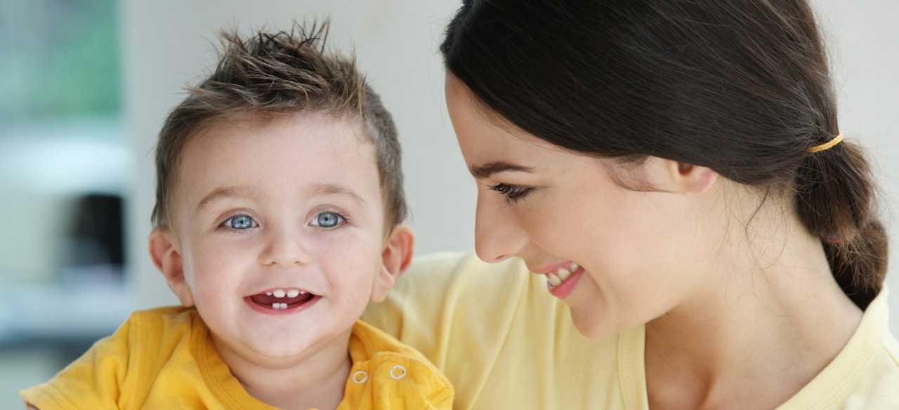 A female caregiver smiles at a little boy