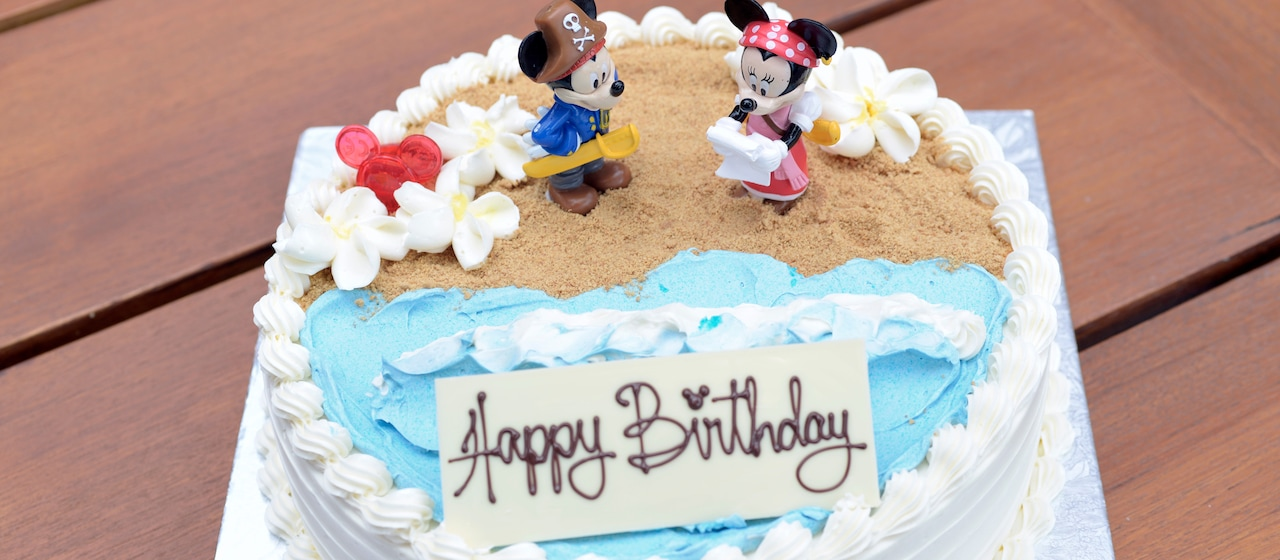 "A decorated layer cake reading ""Happy Birthday"" features Mickey and Minnie Mouse in a beach scene"