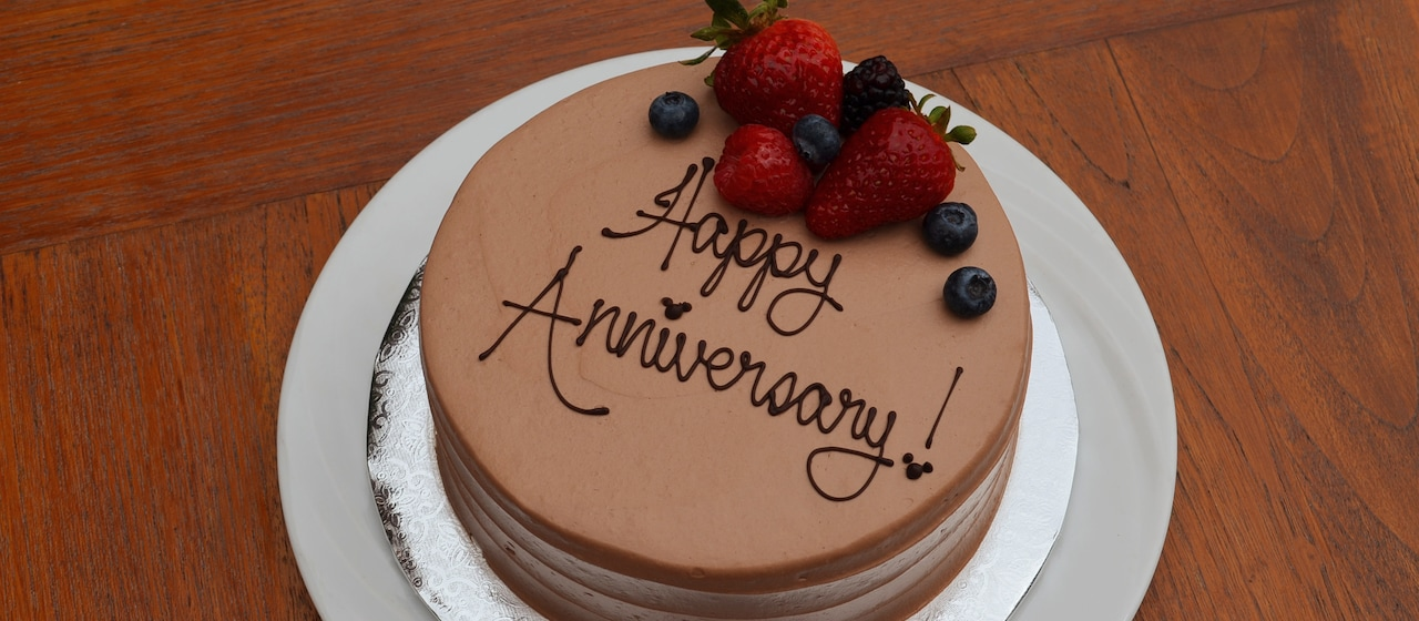 "A cake with chocolate icing is decorated with strawberries, blueberries and ""Happy Anniversary!"" written in icing"