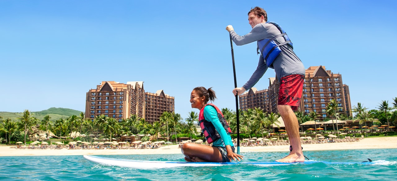 A young woman sits atop a paddleboard as a young man stands and paddles