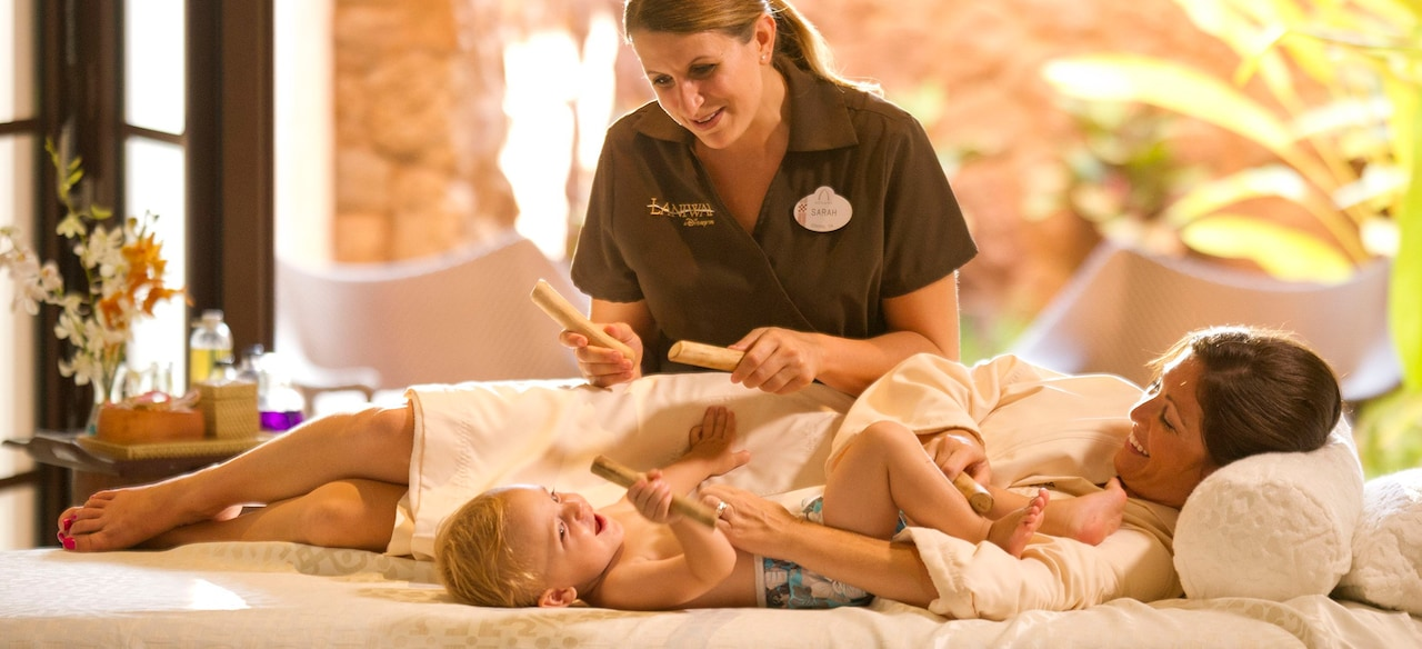 A smiling mother and baby lie on a massage table while a spa practitioner with massage sticks looks on