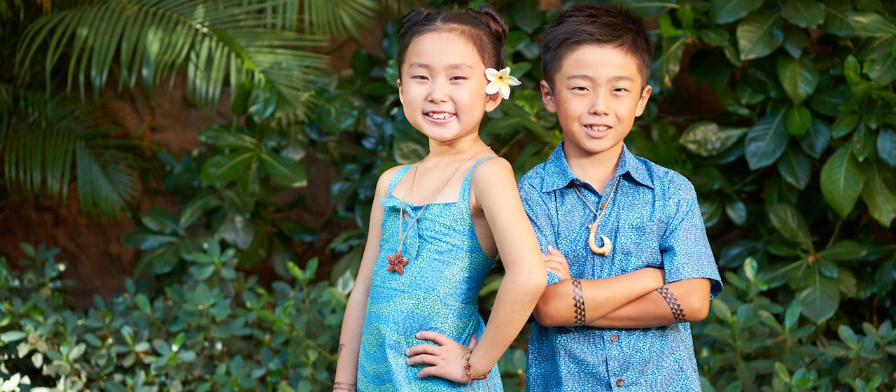 A young boy with tattoos on his crossed arms and a fish hook necklace stands next to girl with a flower behind her ear