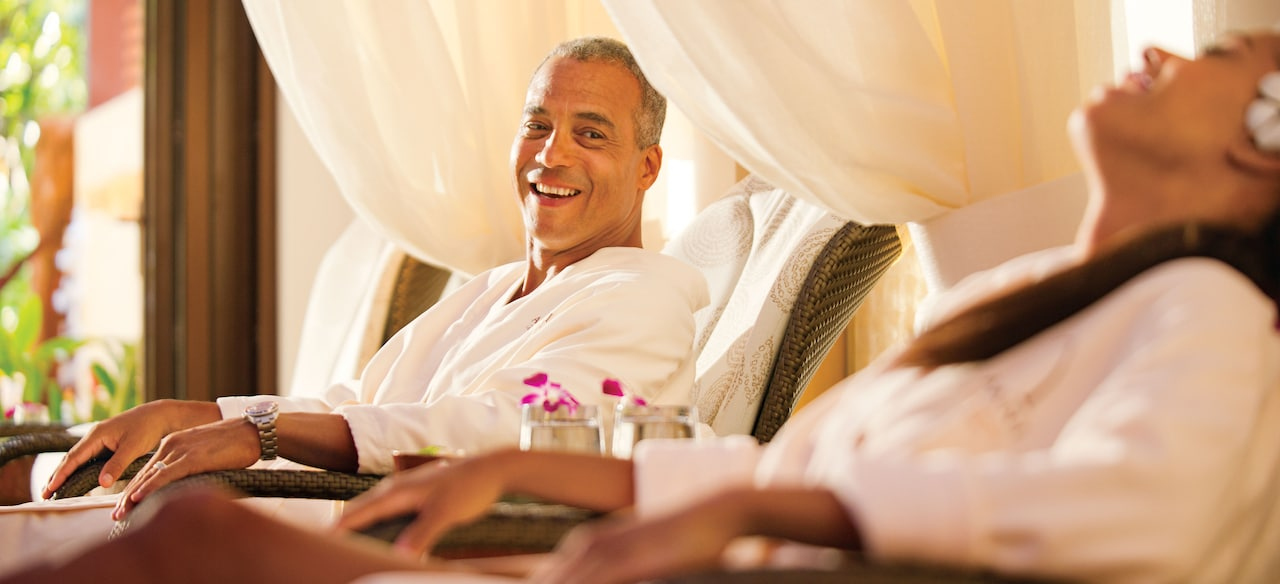A man and a woman wearing Aulani robes sit side by side and relax in Laniwai, a Disney Spa