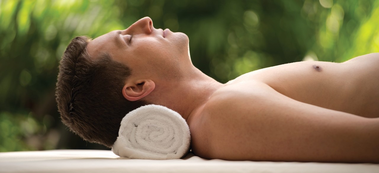 A shirtless man lies back relaxed with his neck supported by a rolled towel
