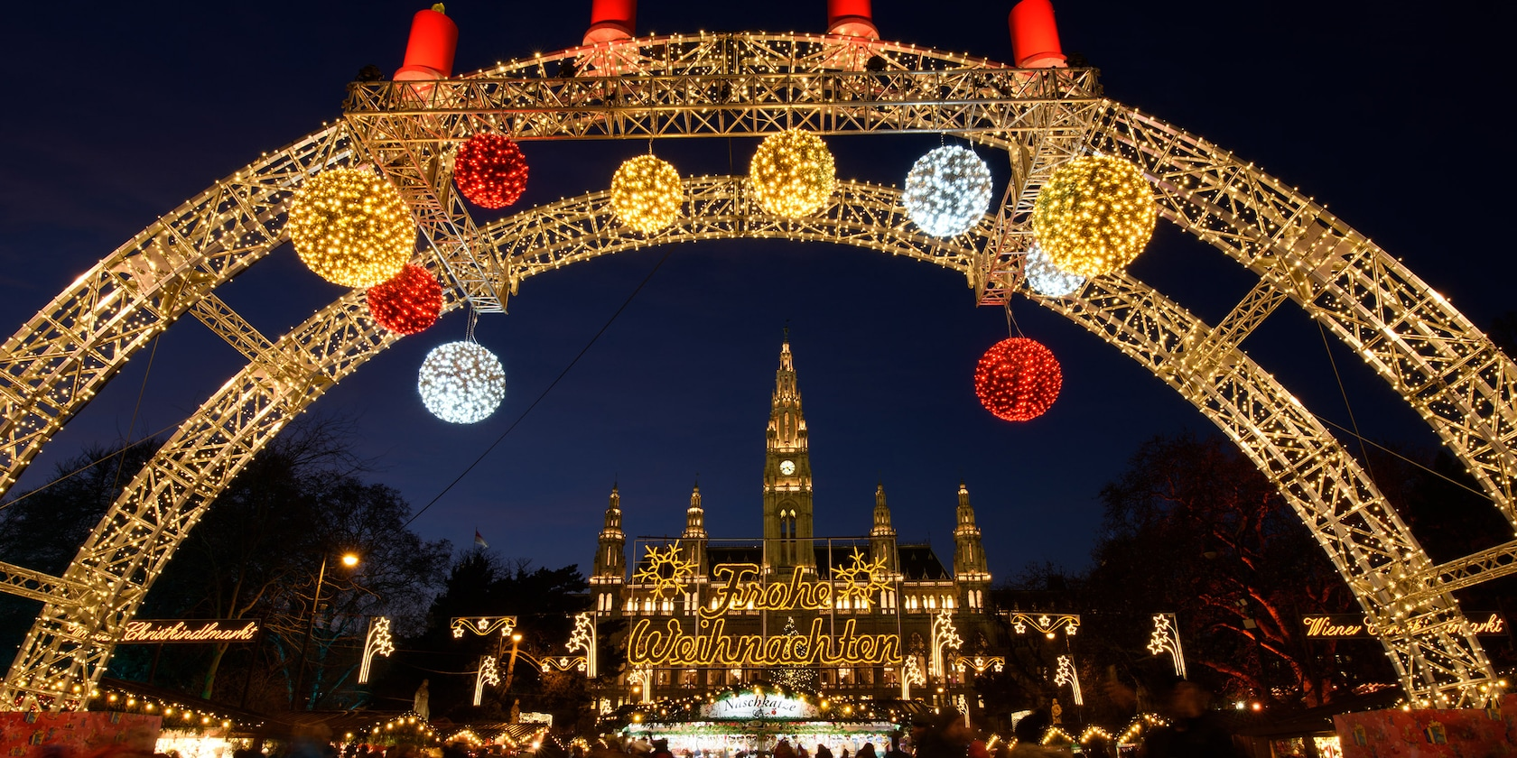 A Christmas market in Vienna is decorated in holiday lights, including a large arc with festive balls of light hanging down and framing a large building with a lighted sign that reads: