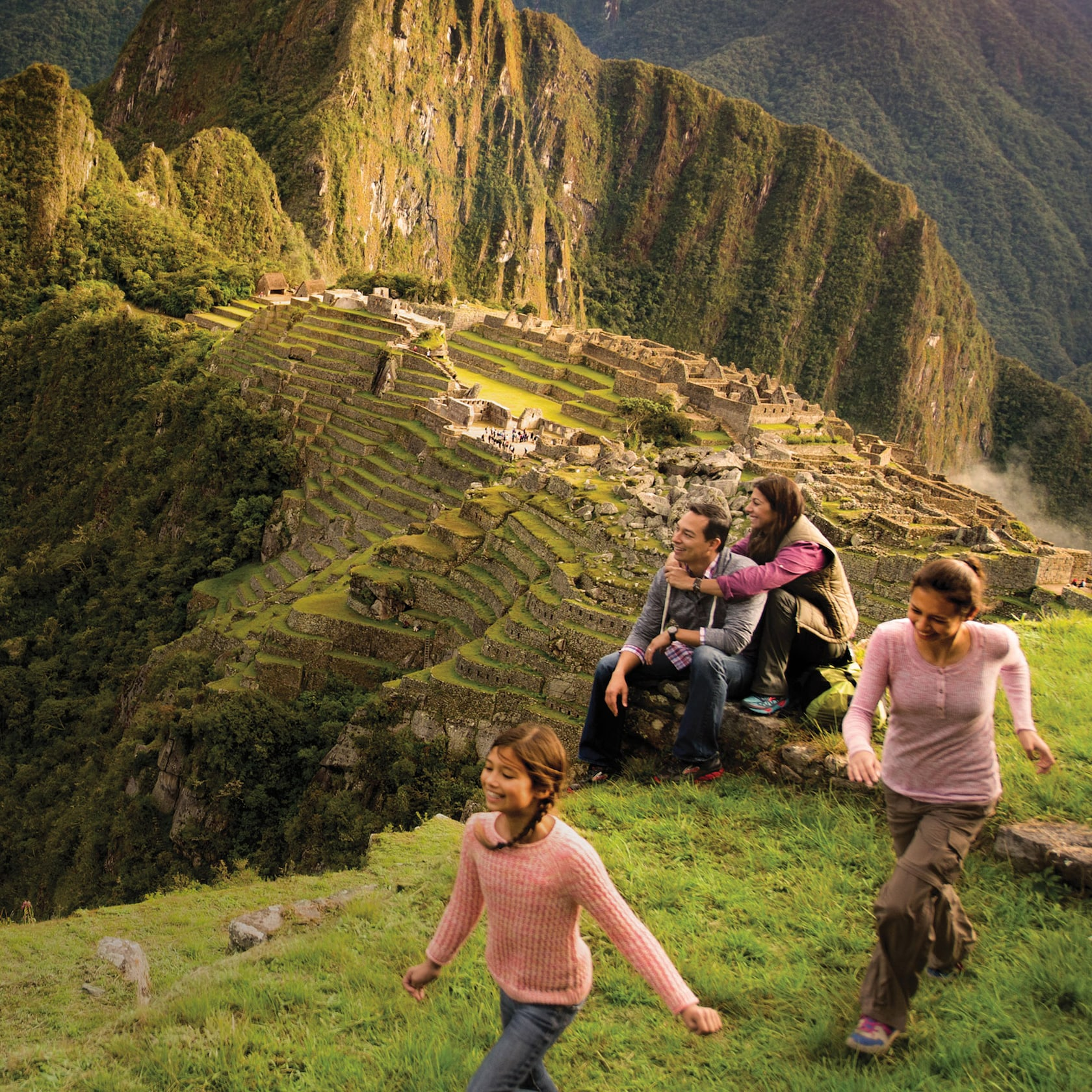 A family views Machu Picchu from a nearby mountaintop