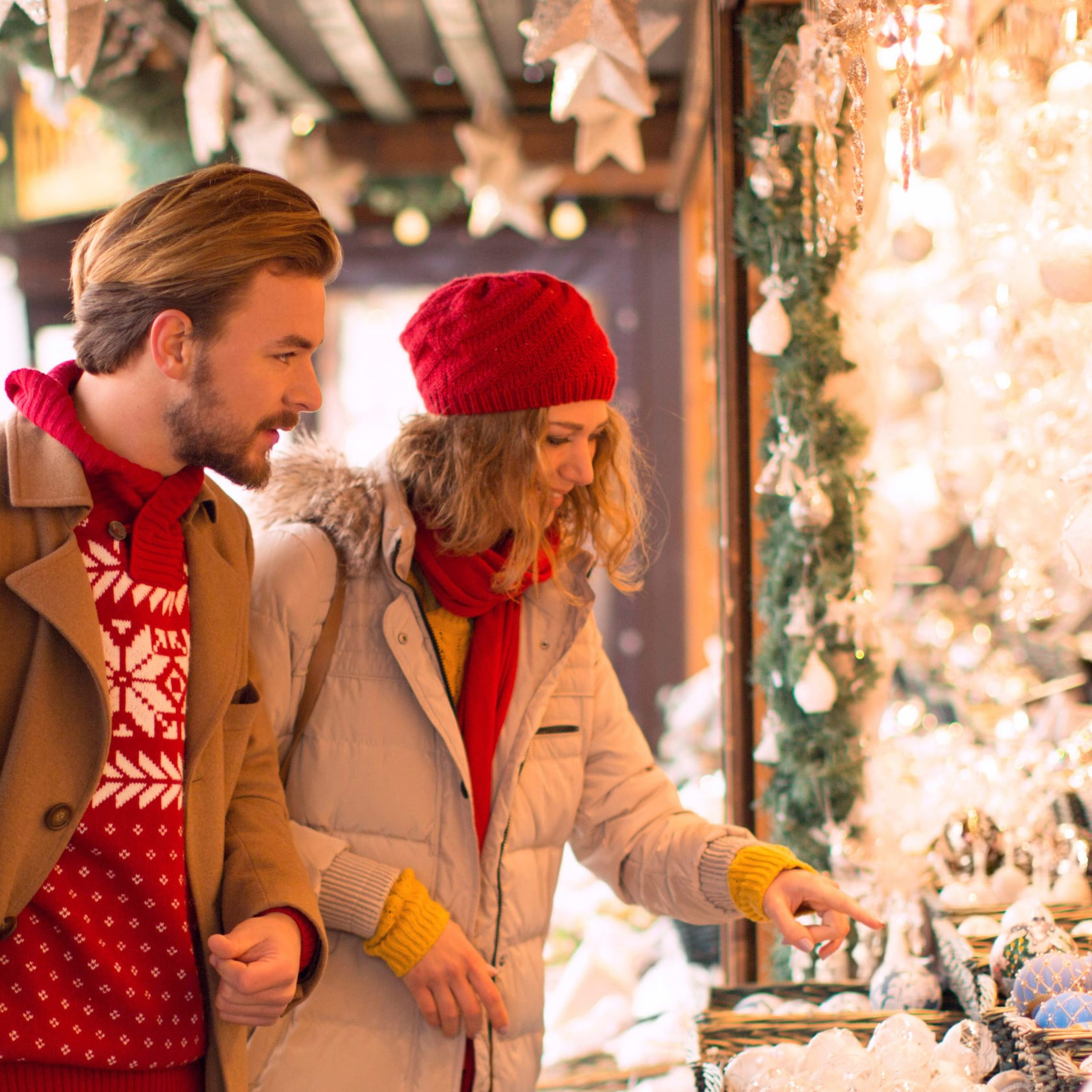 A man and woman look at delicate ornaments at a Christmas Market