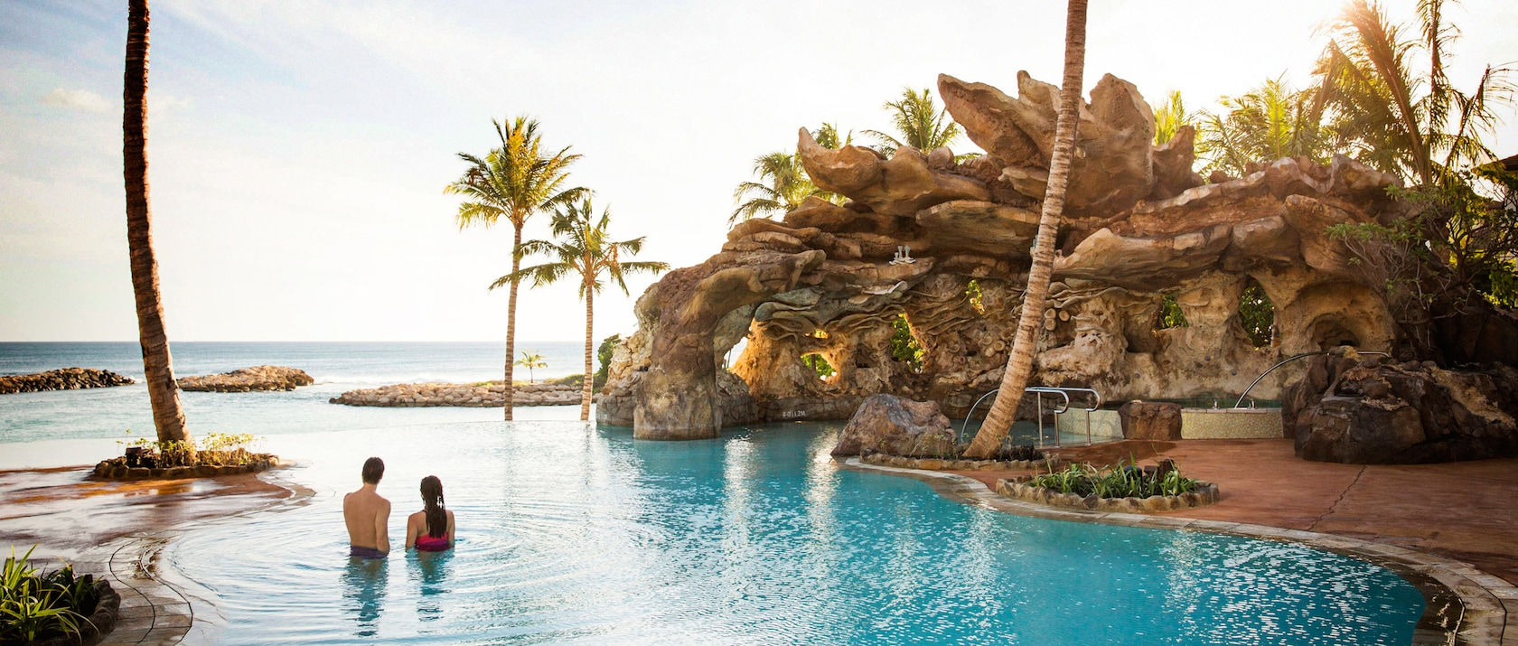 A couple relaxes in the waters of the Ka Maka Grotto oceanfront pool while looking out to the ocean