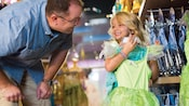 A small girl smiles at her father while holding up a Tinkerbell costume