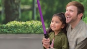 A small girl receives lightsaber training from a Jedi warrior