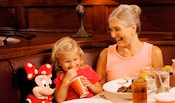 A grinning daughter and mother dine at a booth while seated next to a Minnie Mouse plush doll