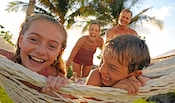 Happy kids lounge in a hammock in their swim suits as their parents watch them underneath palm trees